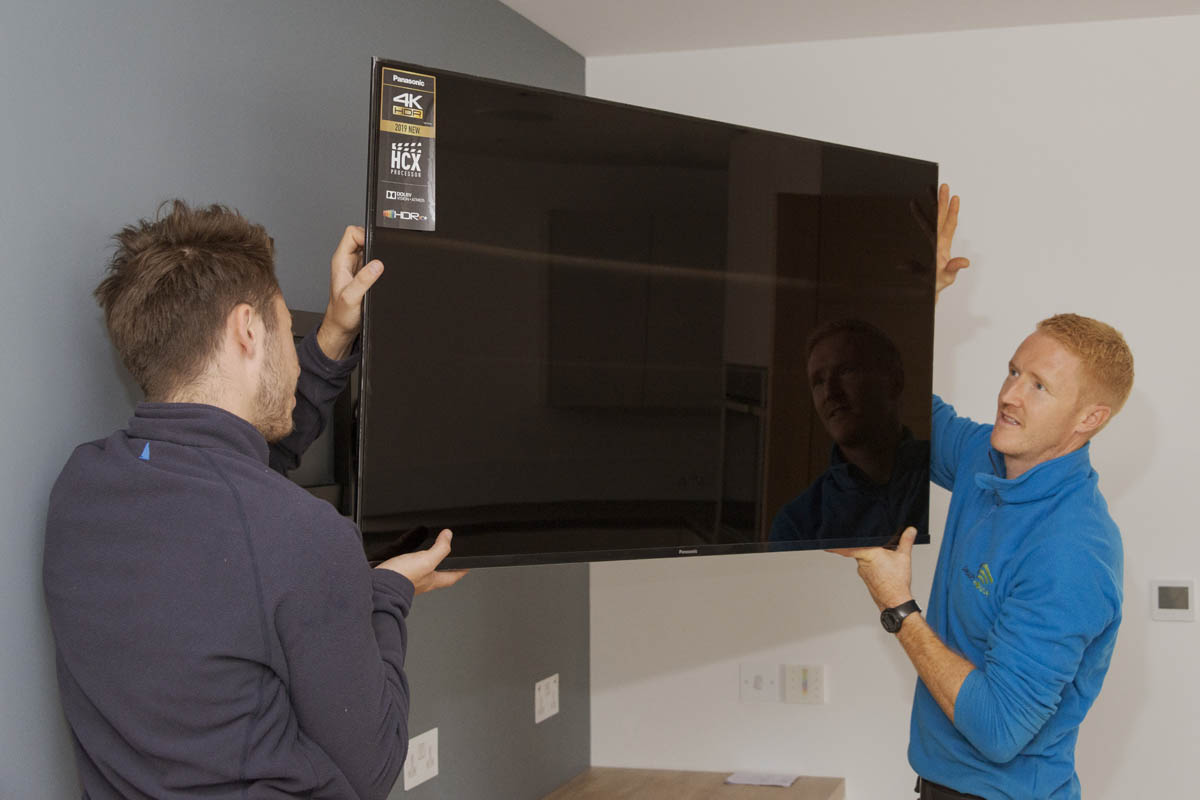 Matt installing a wall-mounted TV in the kitchen